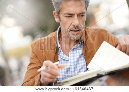 Businessman sitting on public bench, writing on agenda poster