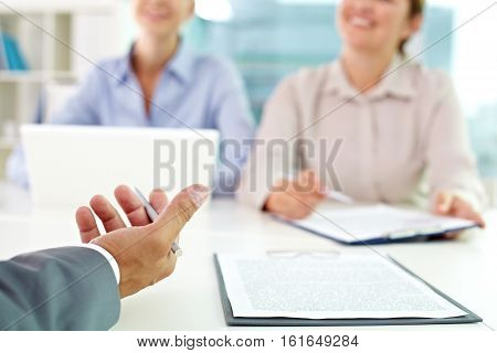Businessman explaining the subject of document to businesswomen