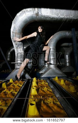 Sexy model in black top and bottom is posing on a production line in an old dark factory with weak lights