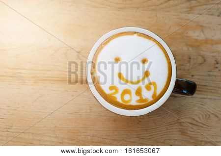 hot coffee with foam milk art 2017 on wooden table
