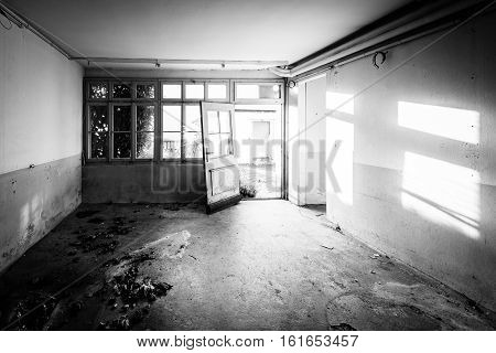 Old abandoned house. The room is destroyed the walls are broken trash on the floor chaos. Selective focus. Black and White.