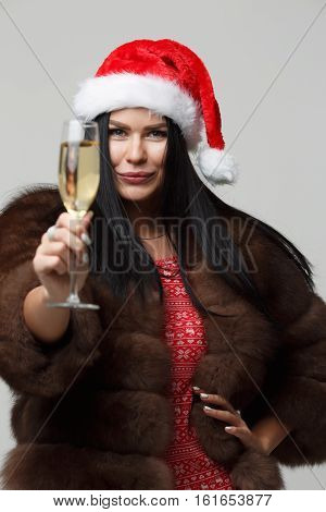 Girl in mink fur coat isolated on gray background with glass of champagne in hand