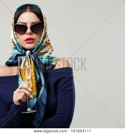 Girl in sunglasses with wineglass on blank gray background