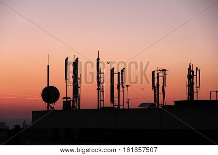 silhouette of GSM transmitters on the roof office building at dusk