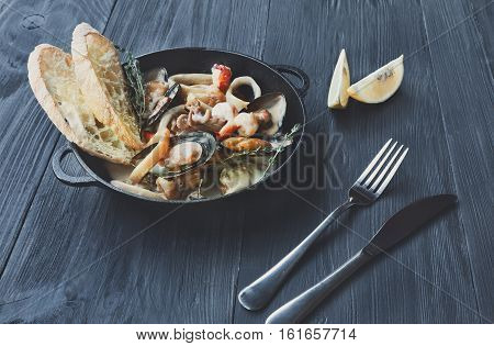 Seafood Stew in Saucepan. Authentic italian restaurant cuisine, healthy delicatessen food. Oysters, shrimps, calamari in white sauce with bruschetta. Bowl on dark black wood background