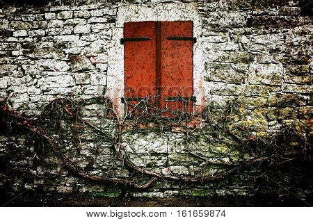 A view of a facade of an abandoned European brick building with a vintage window. Dec 2016