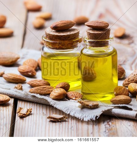 Healthy lifestyle concept. Natural sweet almond essential oil, essence in glass bottle on a rustic wooden table for beauty, spa, therapy, bath