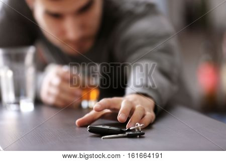 Hand of drunk man and car key on table, closeup. Don't drink and drive concept