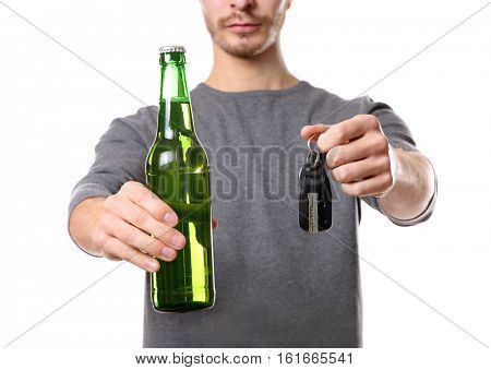 Man with car key and bottle of beer on white background, closeup. Don't drink and drive concept