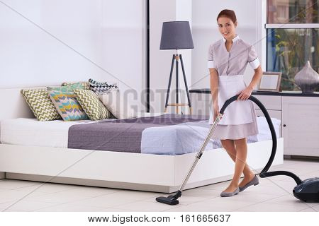 Hotel female chambermaid with vacuum cleaner