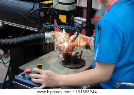 Worker welding repair mold and die part by Laser welding machine in factory.