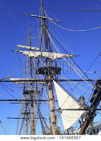 Vintage sailing ship mast and crows nest against a blue sky