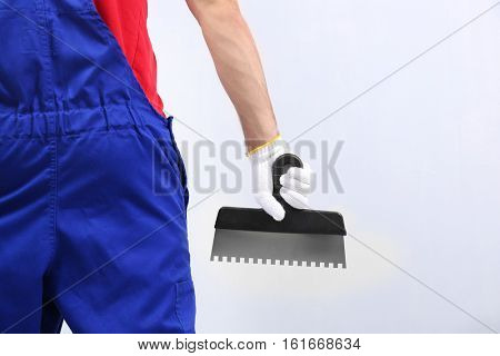 Worker with putty knife on light background, closeup