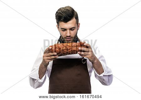 Young man model appearance dressed in ches's apron smelling fresh pastrami isolated on white background