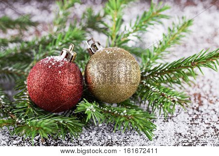 Two decoration balls on fir-tree branch with snow. New Year card design.