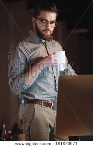 Picture of concentrated designer dressed in shirt and wearing eyeglasses working late at night while drinking tea.
