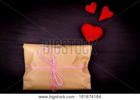 Paper Bag, Gift, Tied With Pink Thread On A Black Background, Crochet Red Hearts, The Day Of St. Val