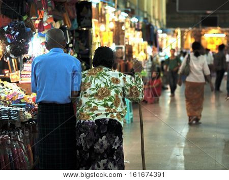 COLOR PHOTO OF HUSBAND HELPING HIS WIFE TO WALK