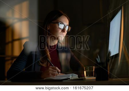Portrait of young tired brunette woman working at desk in front of bright computer screen in dark room and writing notes in notebook