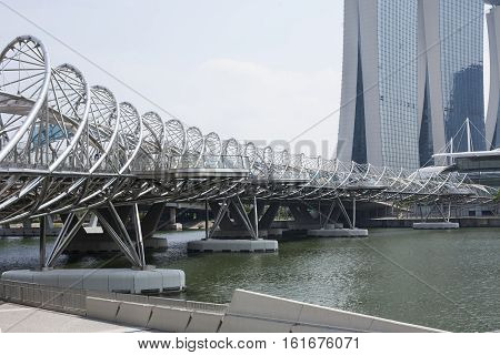 Singapore - 01 November 2014: The Helix Bridge and Marina Bay Sands. It is fabricated from 650 tonnes of Duplex Stainless Steel, 1000 tonnes of carbon steel.