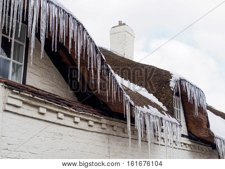 Spiky icicles hanging from the thatched roof of an attractive cottage in Melbourne Derbyshire England in January 2013.