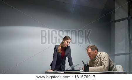 Interrogation scene at police department: intimidating female police officer leaning on desk and looking angrily at guilty mature man seated at it in empty gray room, shot from behind glass wall