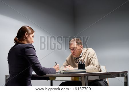 Unkempt middle-aged man facing angry lady boss at desk in empty gray interrogation room, looking guilty and sad while listening to accusations