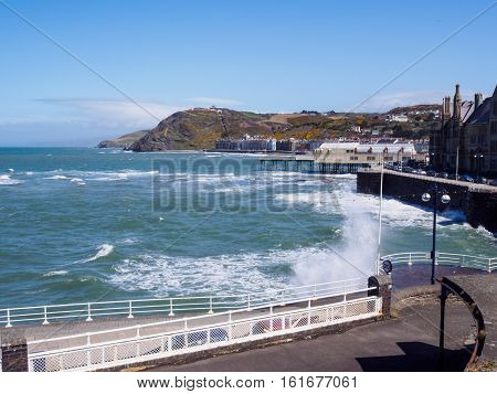 High tide at Aberystwyth an historic market town administrative centre and holiday resort within Ceredigion West Wales. It is located near the confluence of the rivers Ystwyth and Rheidol. poster