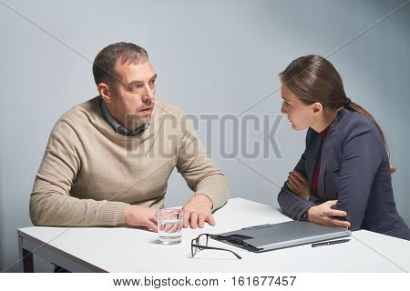 Female officer listening intently to mature man telling her somenthing at table in empty gray interrogation room