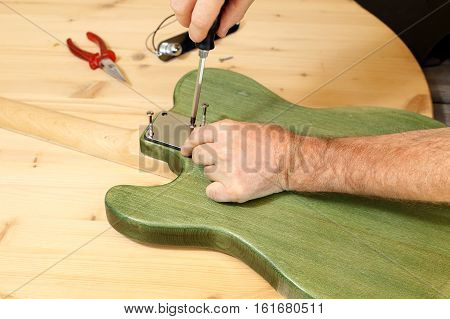 man is building an electrical guitar on a work bench