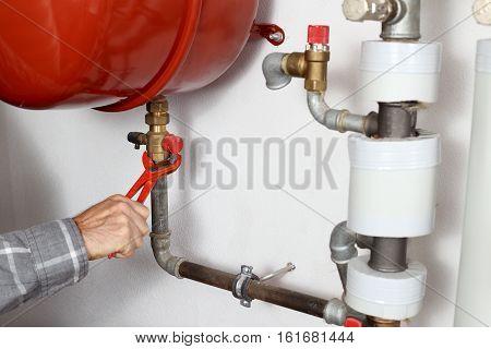 worker repairs a boiler in a heating room