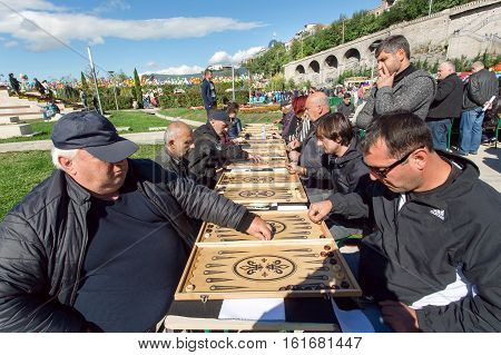 TBILISI, GEORGIA - OCT 16, 2016: Older men playing backgammon on competition at annual autumn city festival Tbilisoba on October 16, 2016. Tbilisoba is traditional festival in capital of Georgia from 1979
