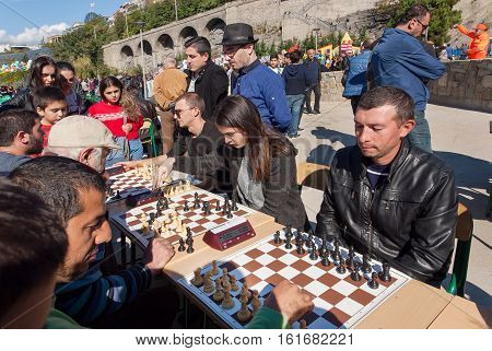 TBILISI, GEORGIA - OCT 16, 2016: Women and men playing chess on competition at annual autumn city festival Tbilisoba on October 16, 2016. Tbilisoba is traditional festival in capital of Georgia from 1979