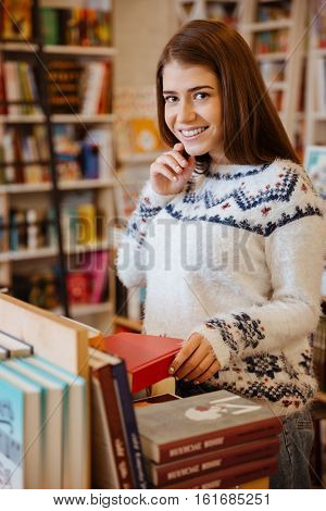 Portrait of a young smiling woman searching for a book in bookstore and looking at camera