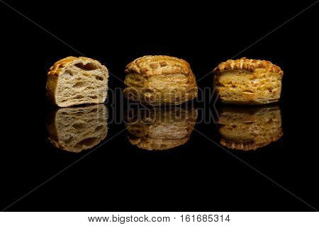 Three small cornbread isolated on black reflective background