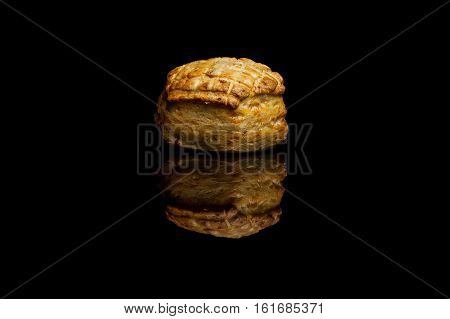 Small cornbread isolated on black reflective background