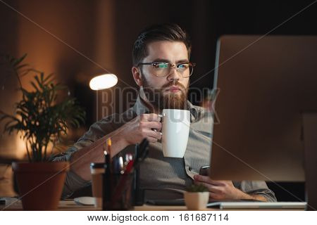 Photo of concentrated young bearded designer dressed in shirt and wearing eyeglasses working late at night while drinking tea.