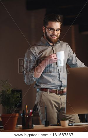 Image of happy young designer dressed in shirt and wearing eyeglasses working late at night while drinking tea.