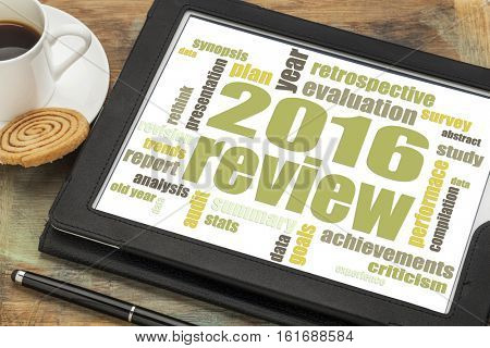 2016 review word cloud on a digital  tablet with a cup of tea