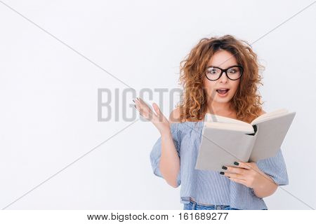 Surprised Woman in singlet and glasses reading book in studio. Isolated gray background