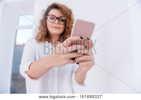 From below image of Woman in glasses and white shirt making selfie over gray background. Focus on phone