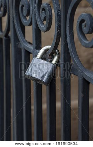 Iron lock on the black forged fence close up