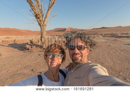 Adult caucasian couple taking selfie at Sossusvlei in the Namib desert Namib Naukluft National Park main travel destination in Namibia Africa.