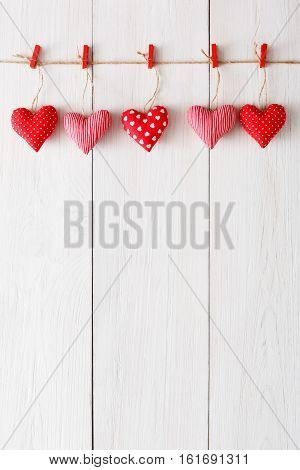 Valentine background with sewed pillow hearts row border on red clothespins at rustic white wood planks. Happy lovers day card mockup, copy space, vertical composition