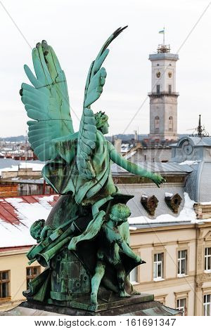 One of the three winged sculptures Wojtowicz. Sculpture music genius at the Lviv Opera and Ballet Theater and Lviv Town Hall tower dominates the town.