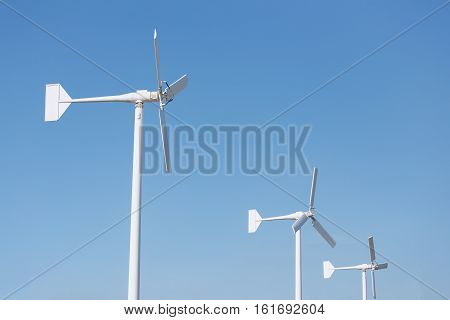 Three white wind turbine for energy generator and reserve on blue sky during sunny day