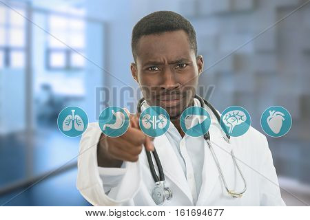 Angry african black male doctor pointing finger at you with stethoscope around his neck, pointing at camera with serious face