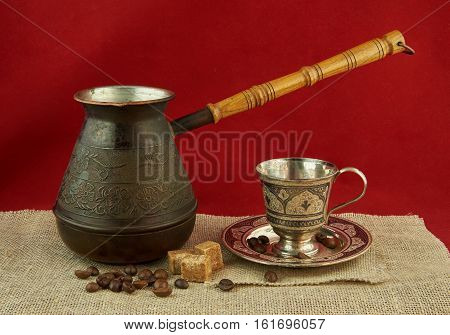 Still life with pots metal cup of coffee sugar and coffee beans Still life with pots metal cup of coffee sugar and coffee beans on a red background