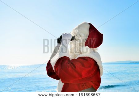 Christmas Vacation - Santa standing on the beach with binoculars, looking for ...  Santa is standing on the beach with binoculars and he is looking for something or somebody. Close-up shot.