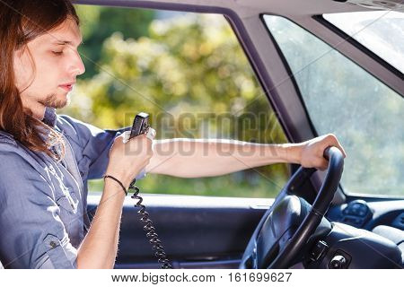 Talking while drive auto walkie talkie comunication concept. Young man driving car using cb radio